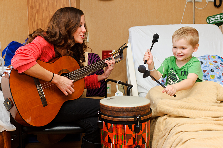 University of Missouri Children's Hospital music therapist, Emily Herzog, plays music with patients at the hospital.