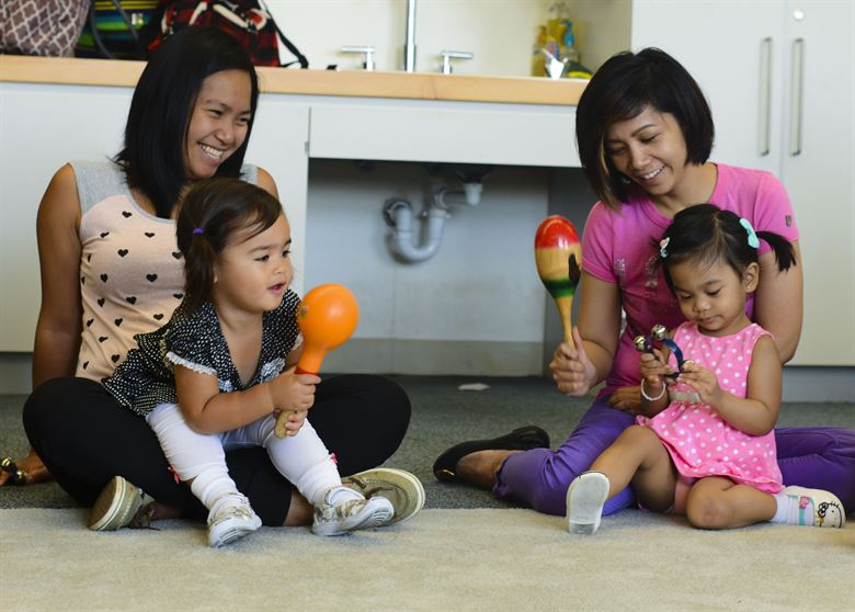 moms with babies playing with percussion toys