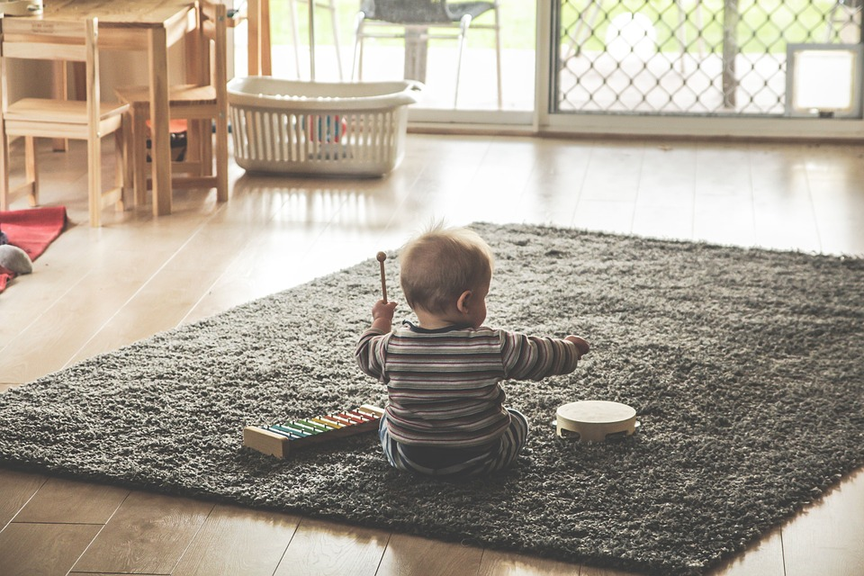 baby on rug playing with percussion toys